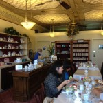 A view of the tea room and their teapots, tea sets, and loose tea to purchase as  a view of the tea room